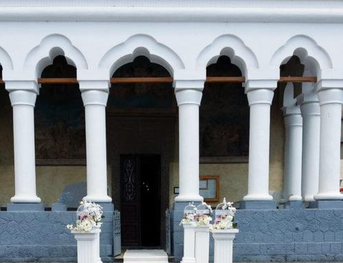 Covor alb, coloane romane cu aranjamente florale în colivii